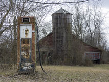 Abandoned Gas Pump and Barn. An old ruined barn and silo and a early 20th c. gasoline pump in a farm field Stock Photography