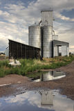 Abandoned grain elevator. Old abandoned grain elevator and shack in Colorado farmland.  Water reflection Royalty Free Stock Photos