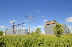 Abandoned grain elevator and bins with an unused telephone pole Royalty Free Stock Photos