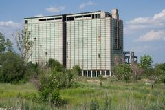 Abandoned grain elevator in overgrown field Stock Photography