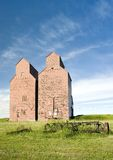 Abandoned Grain Elevators. A pair of abandoned grain elevators standing tall against the blue sky Royalty Free Stock Images