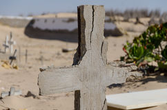 Abandoned graveyard with crumbling stones and crosses in Namib Desert of Angola. The sand is slowly claiming the site back and it seems forgotten and abandoned Stock Photo