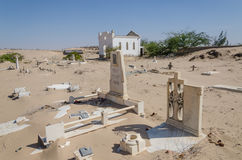 Abandoned graveyard with crumbling stones and crosses in Namib Desert of Angola. The sand is slowly claiming the site back and it seems forgotten and abandoned Stock Photos