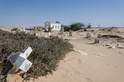 Abandoned graveyard with crumbling stones and crosses in Namib Desert of Angola. The sand is slowly claiming the site back and it seems forgotten and abandoned Royalty Free Stock Photo