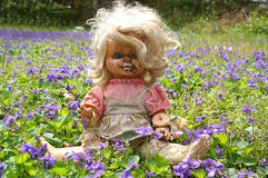 Abandoned Grungy Doll In Flowers Royalty Free Stock Photography