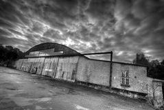 Abandoned hangar. Contrasty abandoned hangar with dramatic clouds Stock Photo