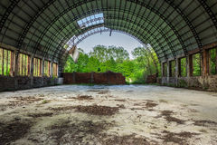 Abandoned hangar in forest. Abandoned ruined hangar with broken round roof in the green forest Stock Image