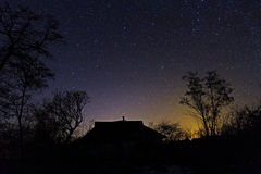 Abandoned his father's house. Happy family silhouette with Milky Way and beautiful night sky full of stars in background making house shape for care and love Stock Photo