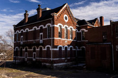 Abandoned, Historic School with Red Brick and White Limestone Lintels. An abandoned, historic school, adorned with red brick and white lintels, is viewed on a Stock Photo