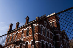 Abandoned, Historic School with Red Brick and White Limestone Lintels. An abandoned, historic school, adorned with red brick and white lintels, is viewed on a Royalty Free Stock Images