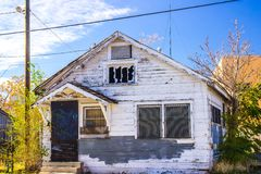 Abandoned Home In Disrepair With Barred Windows. Old Peeling Paint House With Barred Windows & In Disrepair Royalty Free Stock Photos