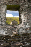 Abandoned home on Great Blasket Island. A roofless house seen through what was once a window in another abandoned home. Part of the abandoned village on Great royalty free stock images