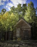Abandoned Home from the 1800`s with Fall Colors in the Mountains. Stunning fall colors of yellow Aspen and assorted green Pine trees on the mountain side stock photos