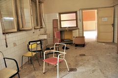 Abandoned hospital room in Italy. Deserted empty room with old , dirty chairs. abandon, desert, empty concept stock photo
