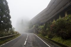 Abandoned hotel on mysterious road with fog