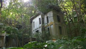 Abandoned hotel resort overgrown by plants in jungle forest, Asia. Nature versus city