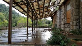 Abandoned hotel terrace with boarded windows and broken roof. Abandoned hotel terrace with boarded windows in traditional stone wall frame, broken terrace roof royalty free stock photography