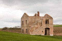Abandoned house. Destroyed abandoned beautiful stone country house without roof on green fields background, Sicily, Italy Royalty Free Stock Image