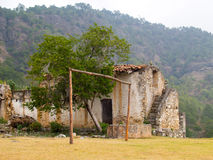 Abandoned house. Abandoned stone house in the mountains near a rustic football field Stock Image