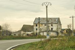 Abandoned house. Abandoned and deteriorated house on a field near a road stock images