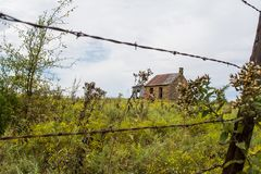 Fence and house. An abandoned house on an acre of farmland Stock Photography