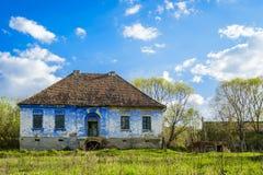 Abandoned house against blue sky. Abandoned blue house against blue sky on green meadow Stock Photography