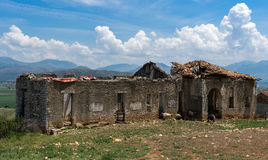 Abandoned House in Albania in front of mountain scenery. Abandoned house near an Albanian road, falling apart and inhereted by goats, all in front of a beautiful stock photography