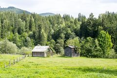 Abandoned house and barn. Abandoned wooden house and barn on fenced plot in Ukrainian Carpathians stock photos