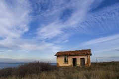 Abandoned house on the beach. destroyed and unsupported house was someone`s home. An old house in the background of a beautiful blue sky and white clouds Royalty Free Stock Photos