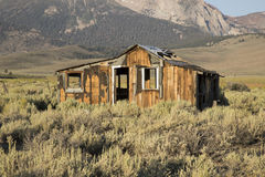 Abandoned house in desert shrub brush. Abandoned wooden house in high desert of Sierra Nevada range in California in shrub brush with mountain backdrop Stock Photo
