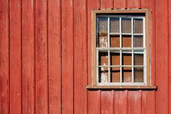 Abandoned house facade with old peeling red wooden wall and grunge broken glass window.  stock images