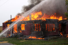 Abandoned House in flame. With firefighters in action Stock Photos