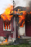Abandoned House in Flames. Abandoned house burning, with flames through windows and door Royalty Free Stock Photo