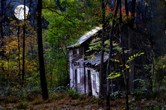 Abandoned House in Forest at Moonrise. A composite of an old abandoned house in the woods with a full moon Stock Photo