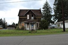 Abandoned house in Granite Falls, WA & x28;front view& x29; with a concrete arch in the front yard stock photo