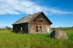Abandoned house in grassy field Stock Images