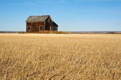 Abandoned house in harvested wheat field in fall Stock Photography