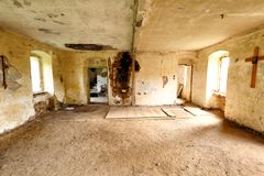 Abandoned house interior with large crucifix. Abandoned house devastated interior with large crucifix on the wall stock photo
