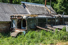 Abandoned house made of rusty old Soviet bus. Green post apocalypse concept.  Stock Photo