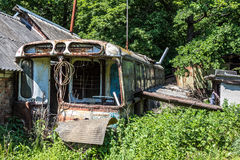 Abandoned house made of rusty old Soviet bus. Green post apocalypse concept.  Royalty Free Stock Image