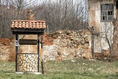 Abandoned house and an old draw well near it. In Bulgarian countryside stock images