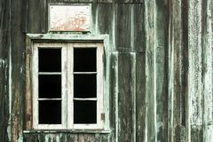 Abandoned house with old peeling grey and green wooden wall and grunge broken white window without glasses Stock Image
