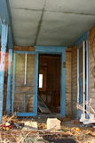 Abandoned House Porch. The porch of an old abandoned house covered with debris and old toys. The screen door hangs open, the main door broken down and laying Royalty Free Stock Images