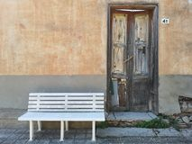 Abandoned house with pristine white bench. In front royalty free stock image