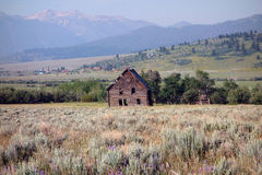 An abandoned house with rain and sun in the background. A tumbledown cabin on a farm in idaho Stock Images