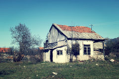 Abandoned house in a rural village. A photograph of an abandoned house with white walls and red tiled roof in a rural area Stock Photos