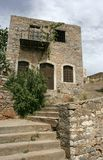 The abandoned house on the small Mediterranean island. The abandoned stone house with the stone stairs and plants on the small Mediterranean island Spinalonga stock images