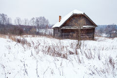 Abandoned house in snow-covered village. Abandoned rustic house in snow-covered village in winter day Royalty Free Stock Images