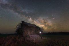 Abandoned house under the Milky Way Galaxy. Man illuminating an abandoned farm house under the Night Sky Stock Photo