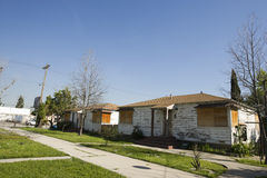 Abandoned Houses With Boarded Up Windows. Pathway and lawns in front of abandoned houses with boarded up windows stock images